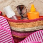 Bag with beach accessories lying on the sand