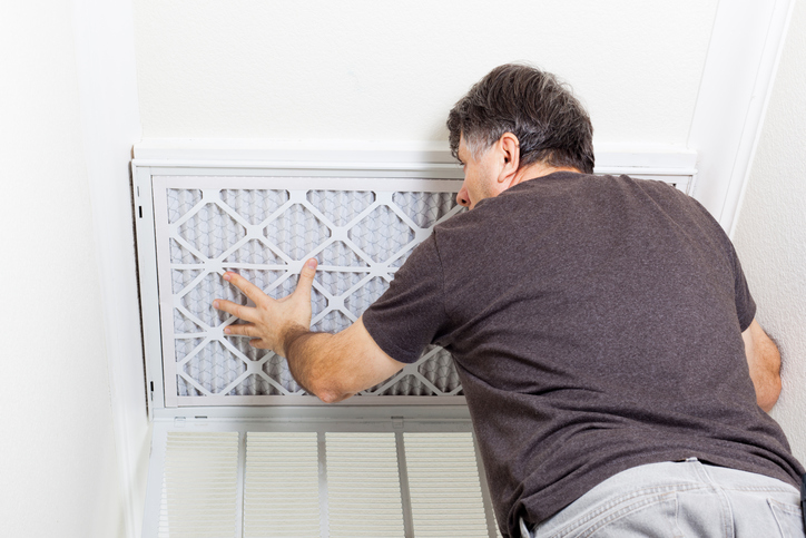 Man replacing a filter on a home air conditioning system.