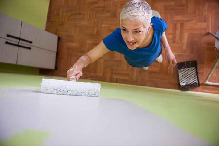 Mature-Senior woman painting the wall at her home