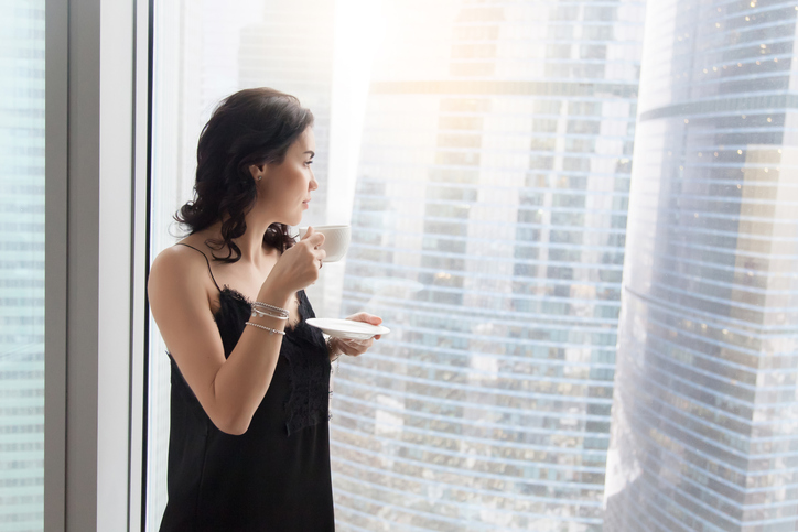 Profile view of calm young woman standing near window with cup of coffee, looking through glass wall at city after waking up in the morning, resting, dreaming before starting working day.