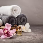 Spa background with orchid flower and massage oil on table